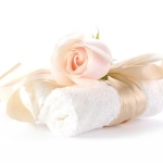 Rose with decorative ribbons over Rolled up Bath Towels